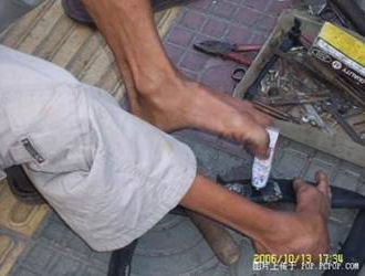 foot-tire03 Handless Man Uses Feet to Repair Tires picture